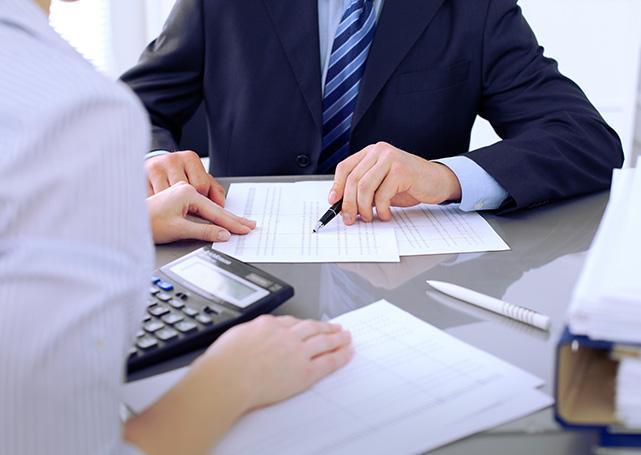 Dwie osoby siedzą przy biurku zdokumentami ikalkulatorem